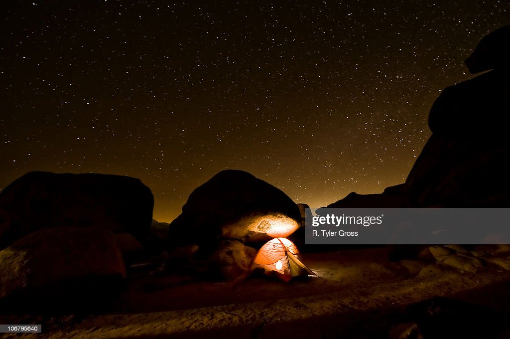 A tent illuminates the night with a star filled sky.