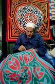 Tent maker sews near Bab Zuwayla gate on the Street of the Tentmakers in Cairo Applique such as this is a mainstay of the Street Egypt | Location...