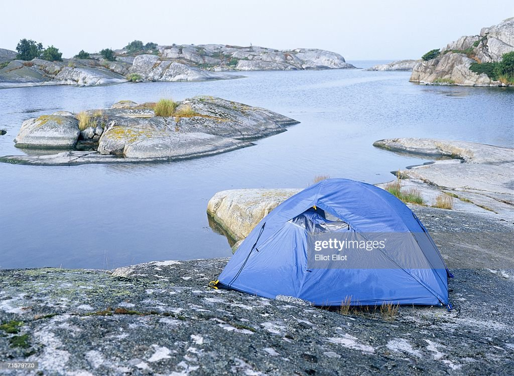 Tent on flat rocks by the sea. : Stock Photo