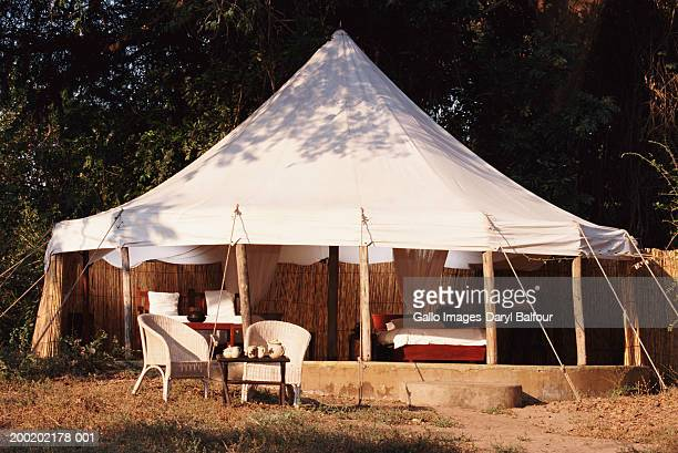 Tented accomodation, table and armchairs in foreground