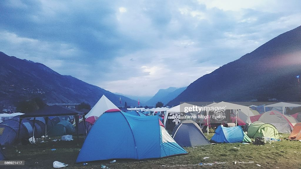 Tents And Mountains Against Cloudy Sky