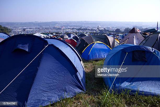 Tents crowded together on a grassy hill for a festival