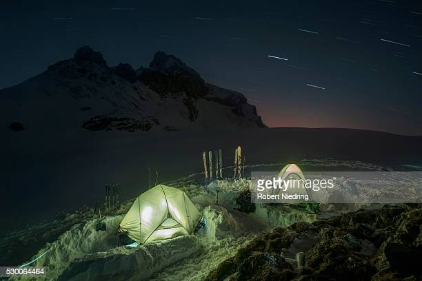 Tents lit up at night in the snow