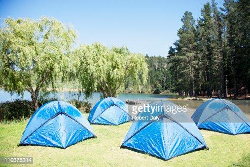 Tents on grass at lakeside : Bildbanksbilder