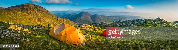 Tents wild camping on idyllic mountain summit panorama Lake District