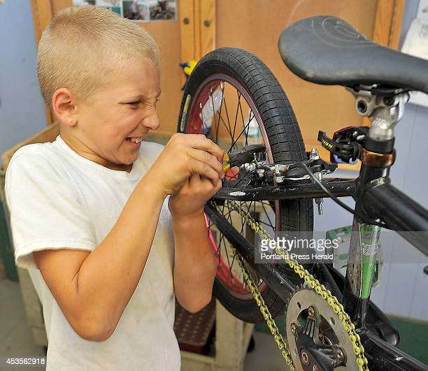 Tenyearold Austin Cantara pulls hard on the wrench as he tightens a nut on the brake pad that he just replaced on his bike in the Community Bicycle...