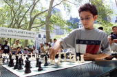 Tenyearold chess prodigy Fabiano Caruana makes his move on one of 15 opponents he took on simultaneously in Bryant Park Caruana playing to promote...