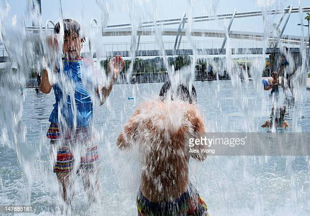 Tenyearold Lilly HwangGeddes of Ithaca New York plays in a fountain at the Yards Park July 5 2012 in Washington DC A record heat wave has been in the...
