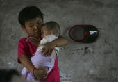 Tenyearold Wang Huaixue holds a baby both of them adopted at Wang Jiayu Orphanage of Sanshilipu Village on July 9 2006 in Yingshang County of Anhui...
