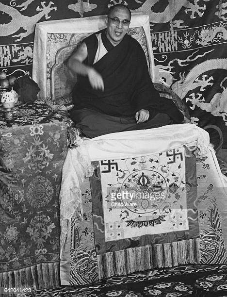 Tenzin Gyatso the 14th Dalai Lama seated on a ceremonial throne in the medieval hall of the abbey at Sutton Courtenay one of the Ockenden Venture...