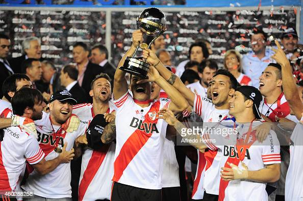 Teofilo Gutierrez and Leonel Vangioni of River Plate lift the trophy and celebrate with teammates after winning a second leg final match between...