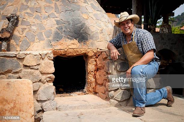 Tequila maker kneeling in front kiln
