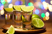 Gold tequila shots with lime fruits on wooden table on bar lights background