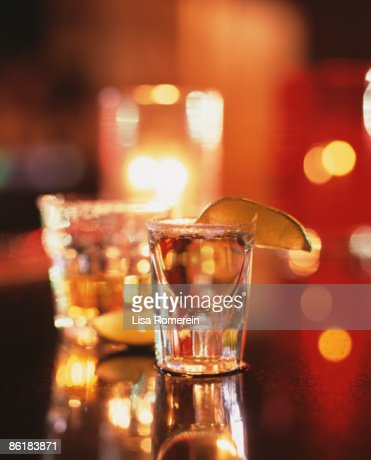 Tequila shots on the bar with salt, lime & candle : Stock Photo