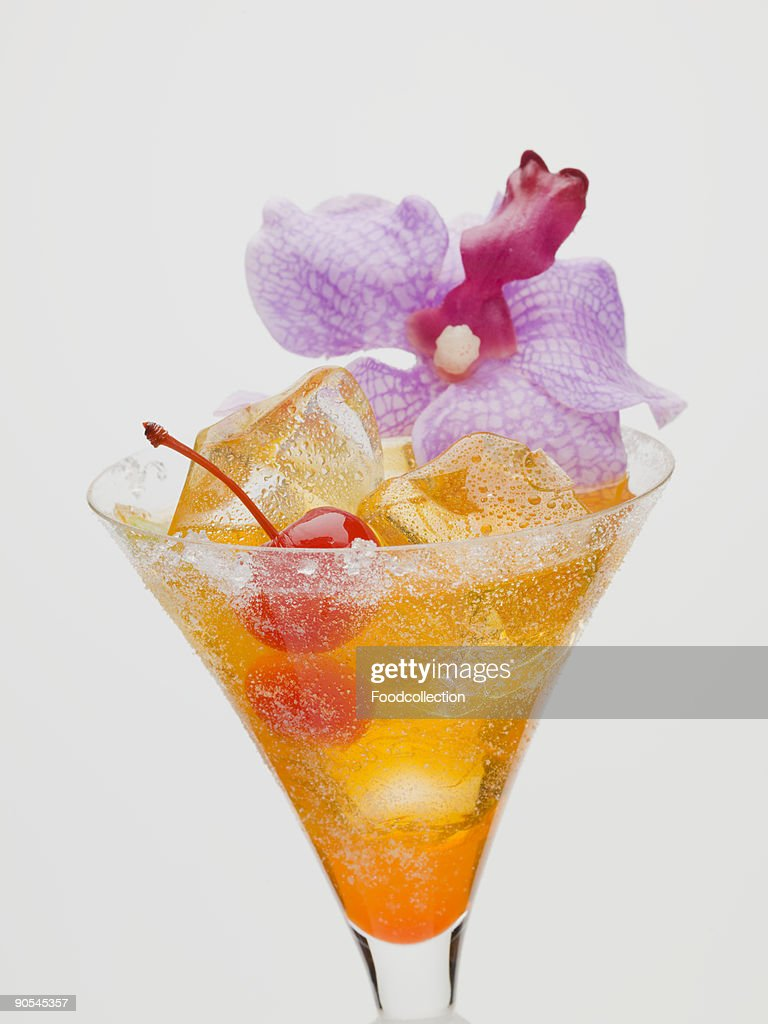 Tequila sunrise with cocktail cherry and orchid : Stock Photo