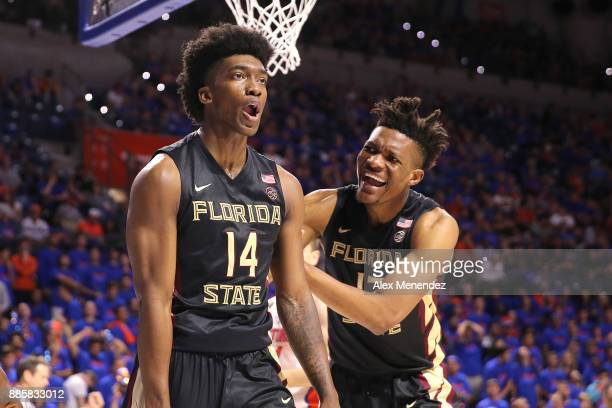 Terance Mann and Ike Obiagu of the Florida State Seminoles celebrate a score and foul during a NCAA basketball game against the Florida Gators at the...