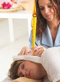 terapist doing ear candling on beautiful woman