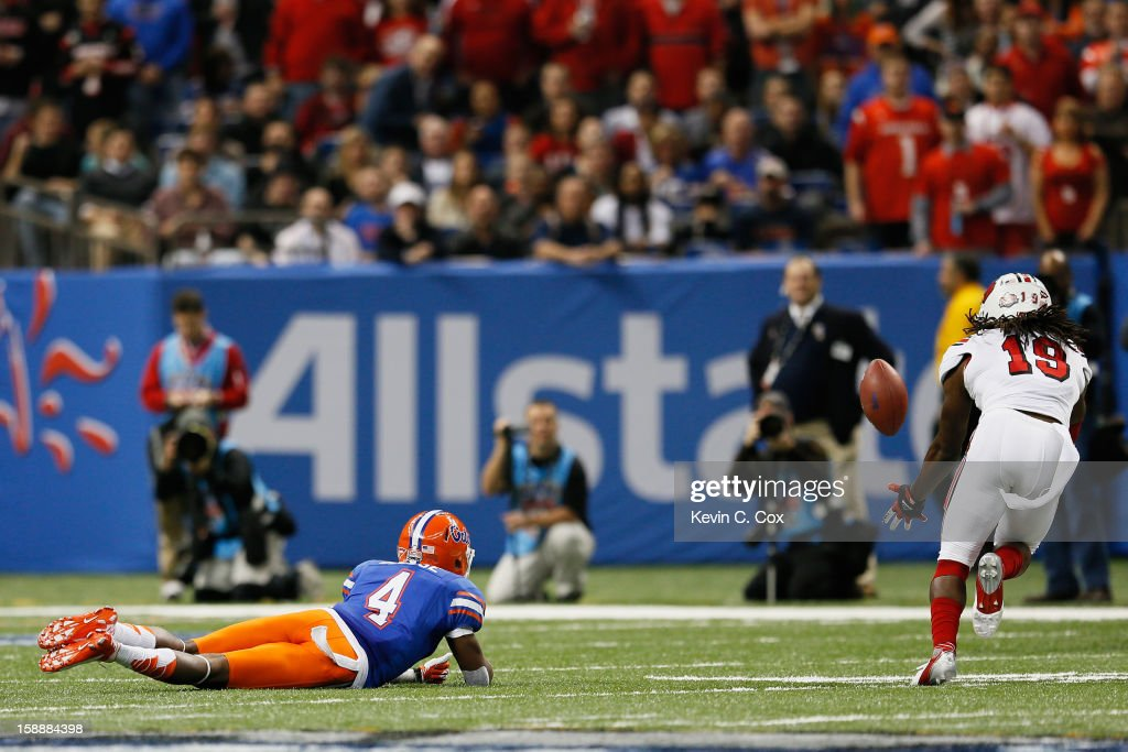 Terell Floyd #19 of the Louisville Cardinals intercepts the ball and runs for a touchdown as Andre Debose #4 of the Florida Gators falls to the field in the first quarter of the Allstate Sugar Bowl at Mercedes-Benz Superdome on January 2, 2013 in New Orleans, Louisiana.