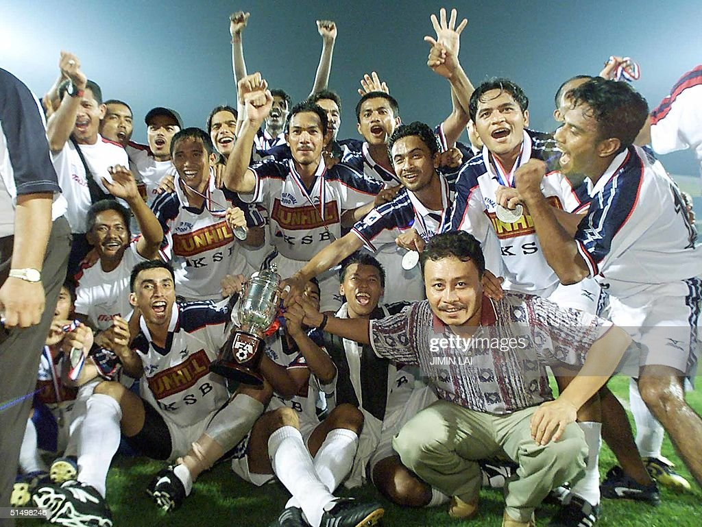 Terengganu football players celebrate with their trophy after winning the finals of the FA Cup 2000 against Penang in Malaysia's northern state of...