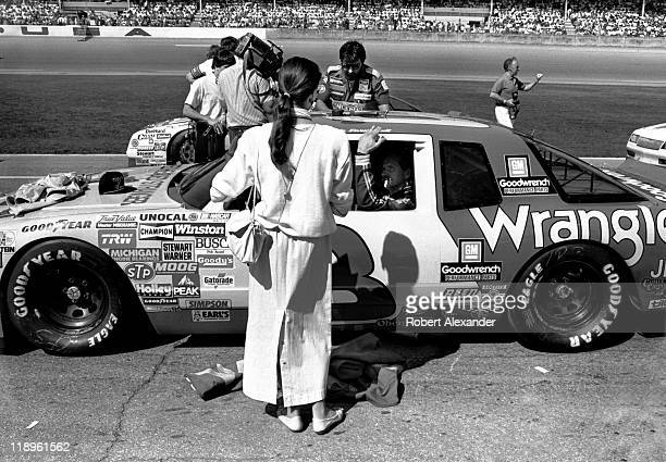Teresa Earnhardt talks with her husband NASCAR driver Dale Earnhardt as the drivers prepare for the start of the 1987 Daytona 500 on February 15 1987...