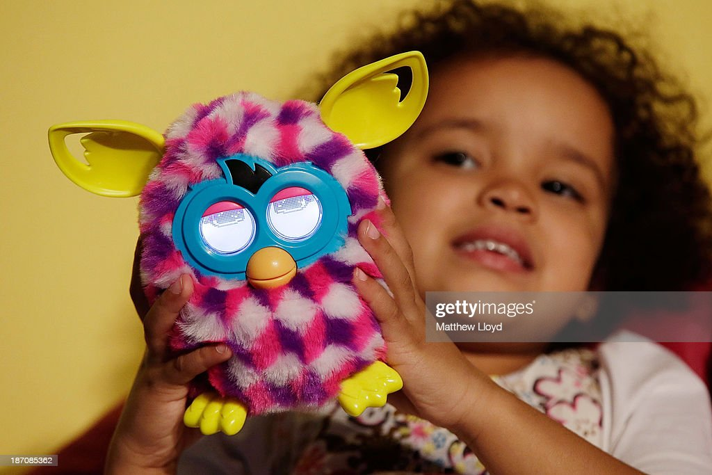 Teresa Kamau, (5), plays with a Furby Boom! at a media event at St Mary's Church in Marylebone on November 6, 2013 in London, England. The Toy Retailers Association's Dream Toys chart, is an independent list of the predicted Christmas top 12 best-selling gifts for children.