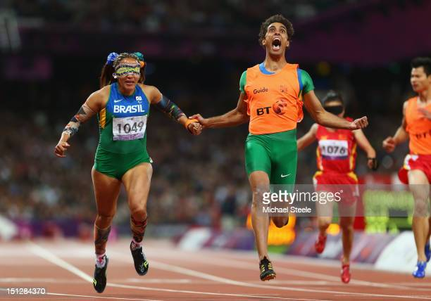 Terezinha Guilhermina of Brazil and guide Guilherme Soares de Santana cross the line to win gold in the Women's 100m T11 Final on day 7 of the London...