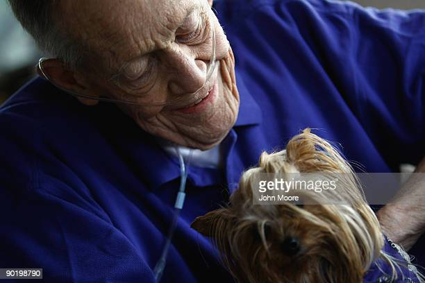 Terminally ill patient Bud Anderson holds therapy dog yorkie Sally Sue during a home hospice visit to his house on August 31 2009 in Lakewood...