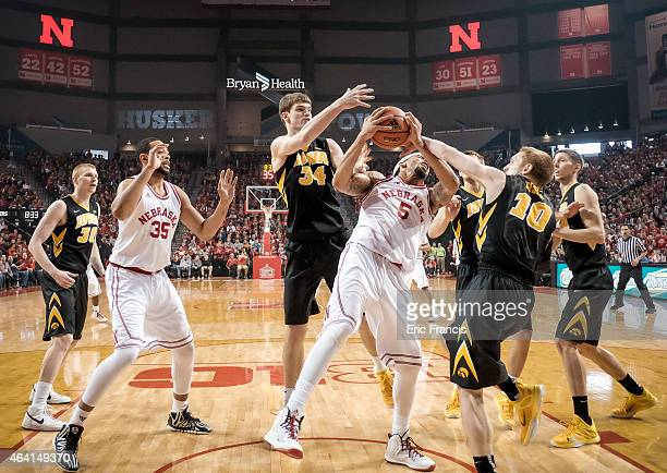 Terran Petteway of the Nebraska Cornhuskers grabs a rebound between Adam Woodbury and Mike Gesell of the Iowa Hawkeyes during their game at Pinnacle...