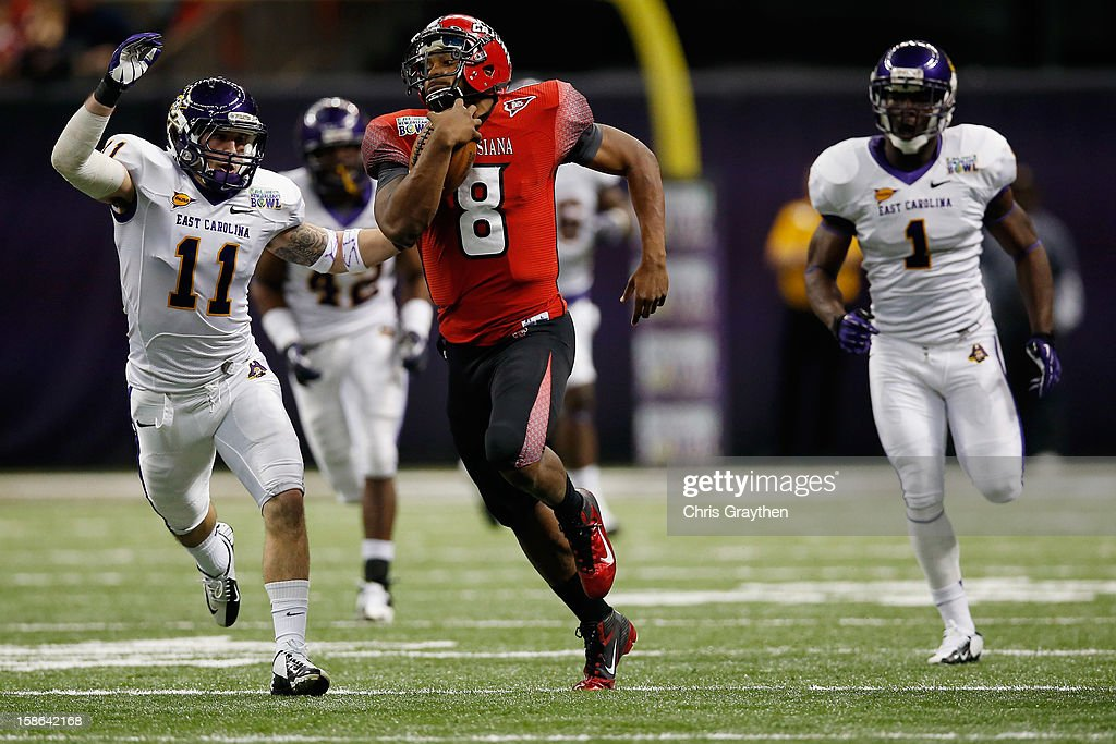 Terrance Broadway #8 of the Louisiana-Lafayette Ragin Cajuns is tackled by Damon Magazu #11 of the East Carolina Pirates during the R+L Carriers New Orleans Bow at the Mercedes-Benz Superdome on December 22, 2012 in New Orleans, Louisiana.