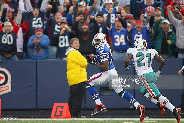 Terrell Owens of the Buffalo Bills crosses the goal line for a 51 yard touchdown ahead of Vontae Davis of the Miami Dolphins at Ralph Wilson Stadium...