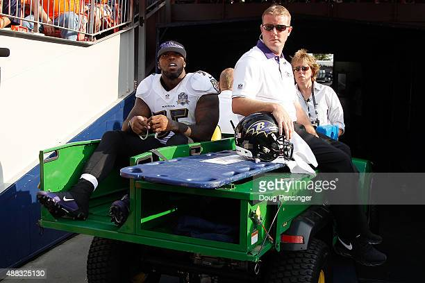 Terrell Suggs of the Baltimore Ravens is taken off the field after tearing his achilles tendon against the Denver Broncos at Sports Authority Field...