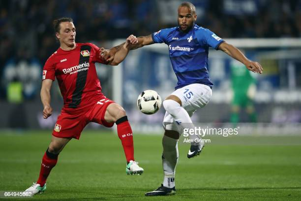Terrence Boyd of Darmstadt is challenged by Julian Baumgartlinger of Leverkusen during the Bundesliga match between SV Darmstadt 98 and Bayer 04...