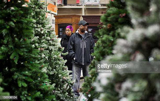Terrence Chester right shops for artificial Christmas trees with his wife Heather Chester at a Home Depot Inc store in Newark New Jersey US on...