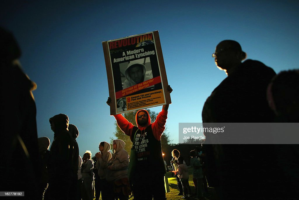 Terrence Davis stands with a sign as he and others hold a vigil at Fort Mellon Park to mark the one year anniversary of when Trayvon Martin was killed on February 26, 2013 in Sanford, Florida. Martin was shot by George Zimmerman on February 26, 2012 while Zimmerman was on neighborhood watch patrol in the gated community of The Retreat at Twin Lakes in Sanford, Florida.