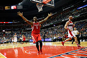 Terrence Jones of the Houston Rockets celebrates after dunking the ball in front of Marcin Gortat of the Washington Wizards in the first half at...