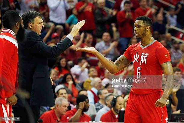 Terrence Jones of the Houston Rockets is greeted near the bench area by head coach Kevin McHale and James Harden during their game against the...