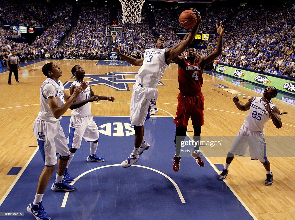 Terrence Jones #3 of the Kentucky Wildcats grabs a rebound over Rakeem Buckles #4 of the Louisville Cardinals during the game at Rupp Arena on December 31, 2011 in Lexington, Kentucky.