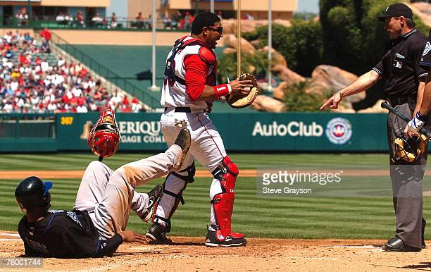 Terrence Long of the Kansas City Royals looks on after scoring as Anaheim Angels catcher Jose Molina right argues the call with home plate umpire...