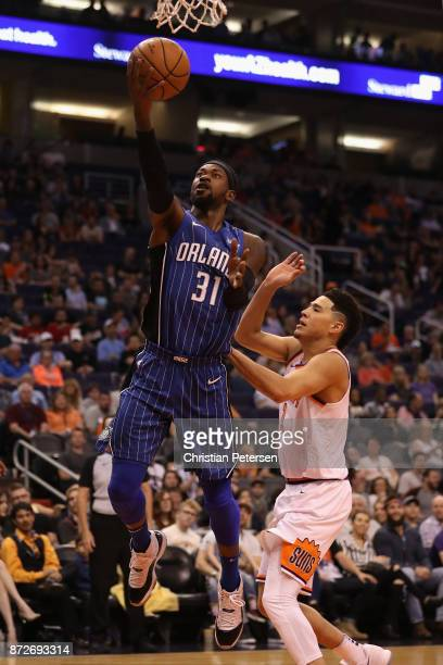 Terrence Ross of the Orlando Magic lays up a shot past Devin Booker of the Phoenix Suns during the first half of the NBA game at Talking Stick Resort...