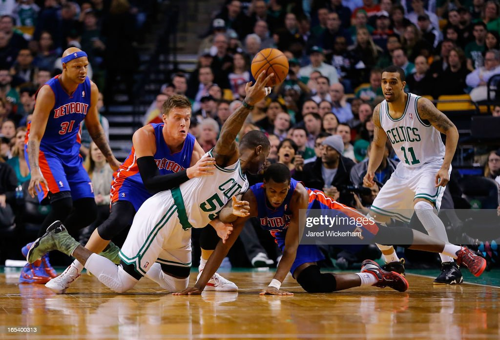 Terrence Williams #55 of the Boston Celtics passes the ball from the floor over Jonas Jerebko #33 and Khris Middleton #32 of the Detroit Pistons during the game on April 3, 2013 at TD Garden in Boston, Massachusetts.