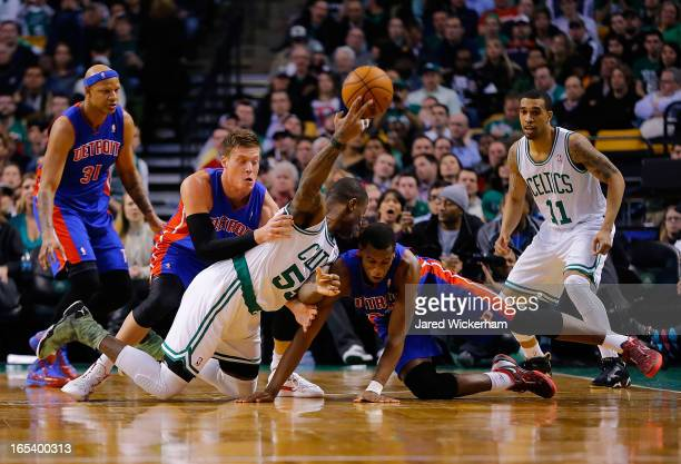 Terrence Williams of the Boston Celtics passes the ball from the floor over Jonas Jerebko and Khris Middleton of the Detroit Pistons during the game...