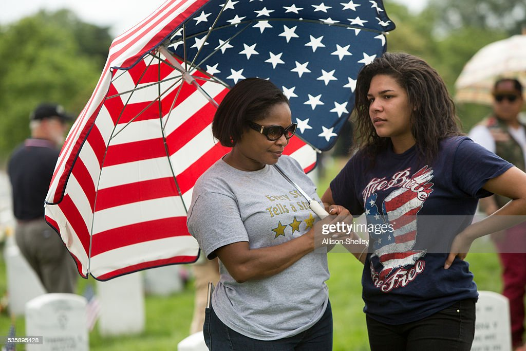 Terri Dunn Campbell of Virginia Beach, Virginia, stands with her daughter Nicole Campbell, 18, at the grave of her oldest son Kielin Terrell Dunn, who was killed at age 19 in Afghanistan in 2010, in Section 60, the burial ground for military personnel killed since 2001, at Arlington National Cemetery on May 30, 2016 in Arlington, Virginia.
