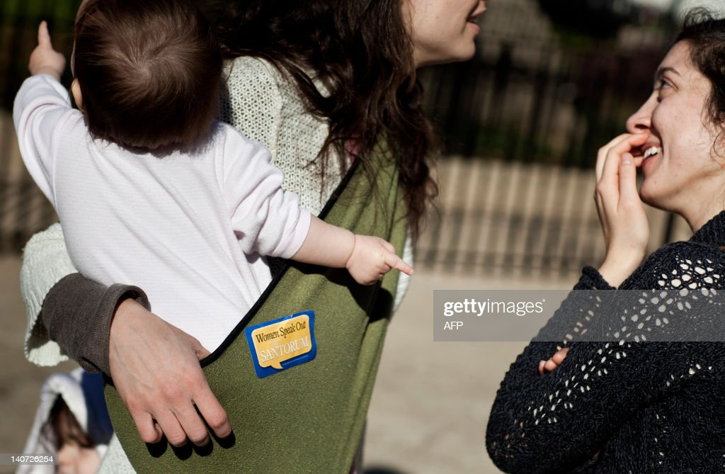 Terri Fike speaks with her friend Samantha Mlot while holding her baby after listening to Santorum supporters speak outside the Georgia State Capitol...