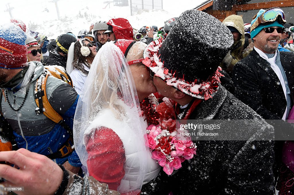 Terri Looft, in red and white, left, kisses her husband Scott Wilson, in top hat, during the 25th annual Mountaintop Matrimony Valentine's day wedding ceremony on February 14, 2016 at the Loveland Ski area near Georgetown, Colorado. The couple got married last year and decided to renew their wedding vows. The ceremony was held at Ptarmigan Roost cabin at the top of Ptarmigan lift. Approximately 100 couples got married or renewed their vows with minister Harry Heilmann, of the Universal Life Church, overseeing the ceremony.