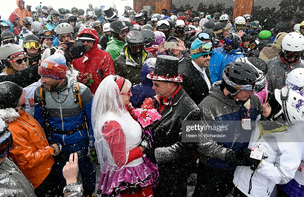 Terri Looft, in red and white, renews her vows with husband Scott Wilson, in top hat, during the 25th annual Mountaintop Matrimony Valentine's day wedding ceremony on February 14, 2016 at the Loveland Ski area near Georgetown, Colorado. The couple got married last year and decided to renew their wedding vows. The ceremony was held at Ptarmigan Roost cabin at the top of Ptarmigan lift. Approximately 100 couples got married or renewed their vows with minister Harry Heilmann, of the Universal Life Church, overseeing the ceremony.