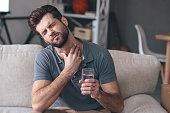 Frustrated handsome young man touching his neck and holding a glass of water while sitting on the couch at home