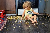 Little girl spills a snack all over the floor, but seems content to eat it anyway