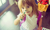Little girl draws on her face with a marker