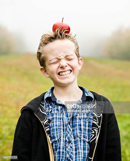 Verängstigt Junge mit einem Apfel auf dem Kopf