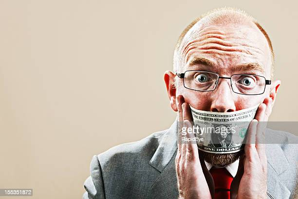 Terrified businessman tries to remove dollar bill gag